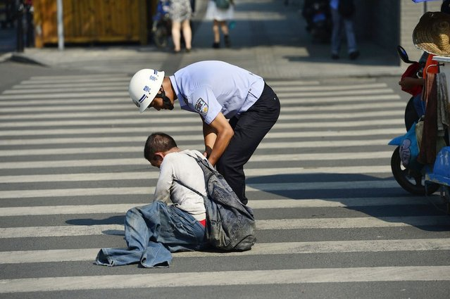 A beggar who lay at the side of a road pretending he had no legs was moved on by police who made him stand up and walk away. The man lay slumped on his front in Chengdu, in Sichuan Province, China, with his legs tucked under him, and his jeans stretched out to make it appear he had no legs. He is approached by a police officer, who bends down and talks to him for some moments. (Photo by Rex Features)