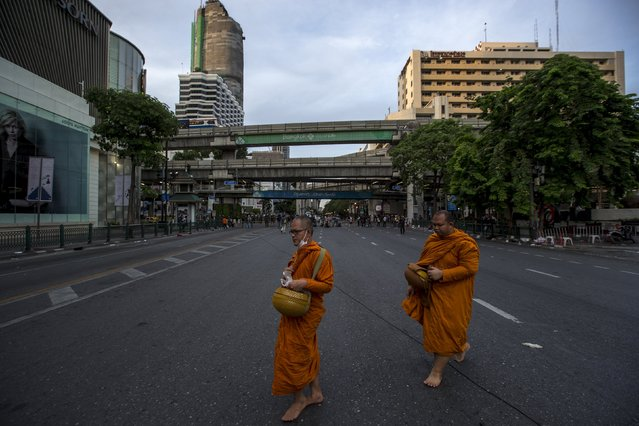 Thai Buddhist monks walk past near the scene of a blast in central Bangkok August 18, 2015. (Photo by Athit Perawongmetha/Reuters)