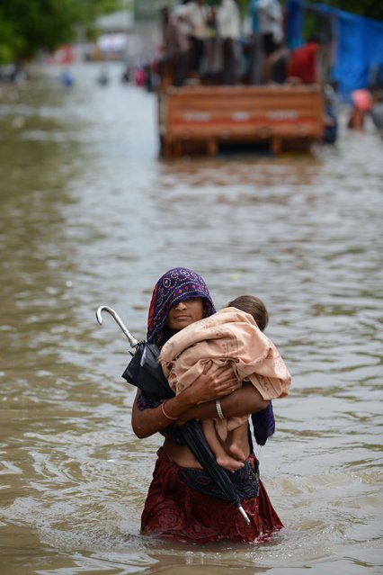 An Indian mother holds her child as she wades through floodwaters in Ahmedabad on July 30, 2014. (Photo by Sam Panthaky/AFP Photo)