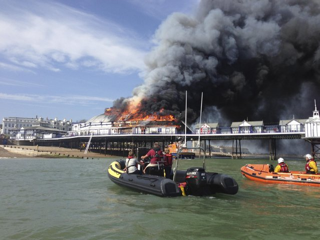Fire and smoke engulf part of the pier in Eastbourne, southern England July 30, 2014. A Victorian-era seaside pier at Eastbourne on Britain's south coast was badly damaged when fire broke out in an amusement arcade on Wednesday. Flames could be seen leaping from the roof of the two-storey structure and East Sussex Fire and Rescue Service said a large plume of smoke was rising above the town. No injuries were reported. (Photo by Benjamin Hall/Reuters)