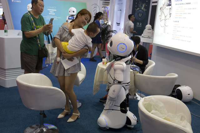 A woman holds a child near a robot a day before the opening of the World Robot Conference held in Beijing, China, Tuesday, August 22, 2017. (Photo by Ng Han Guan/AP Photo)