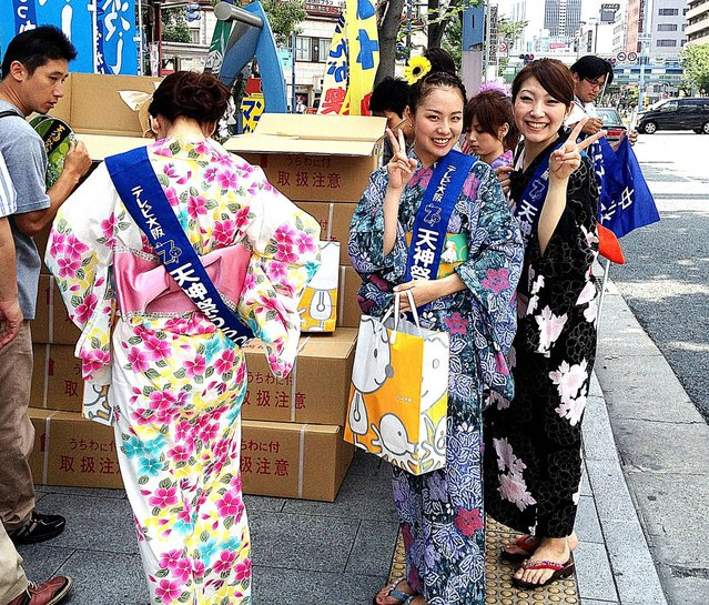 Girls prepare for the famous Tenjin Matsuri (festival) in Minami-Mirimachi, Osaka on July 24, 2012. The two-day festival is one of the three biggest summer festivals in Japan, along with the Gion festival in Kyoto and the Kanda festival in Tokyo. The 1,000-year-old festival culminates in a huge fireworks display. (Photo by Kamasami Kong)