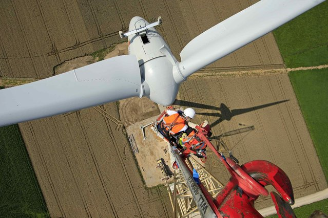 Employees work on a crane above an E-70 wind turbine manufactured by German company Enercon for La Compagnie du Vent (GDF SUEZ Group) during its installation at a wind farm in Meneslies, Picardie region, July 31, 2014. (Photo by Benoit Tessier/Reuters)