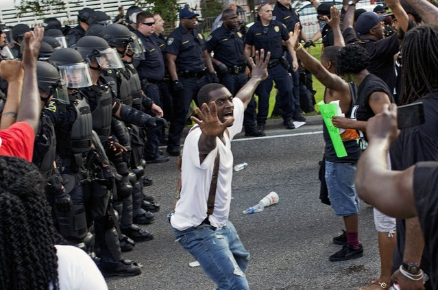 A man attempts to stop protesters from engaging with police in riot gear in front of the Baton Rouge Police Department headquarters after police attempted to clear the street in Baton Rouge, La., Saturday, July 9, 2016. Several protesters were arrested. (Photo by Max Becherer/AP Photo)