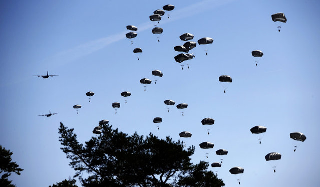 """Paratroopers take part in an exercise of the U.S. Army Global Response Force in Hohenfels, Germany,  Wednesday, August 26, 2015. Around 5000 soldiers from 11  NATO nations participated in simultaneous multinational airborne operations across Germany, Bulgaria, Italy and Romania called """"Exercise Swift Response"""". The exercise was the largest Allied airborne training in Europe since the end of the Cold War. (Photo by Matthias Schrader/AP Photo)"""