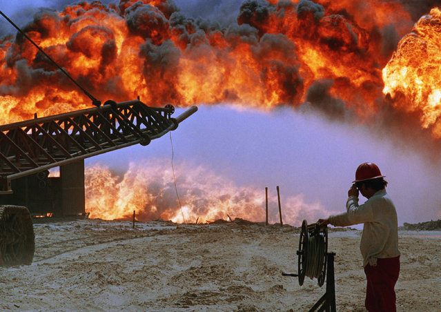 "After an unsuccessful attempt to extinguish one of the biggest oil fires in Kuwait, the well known as ""Hollywood"" continues to pour black smoke into the atmosphere as if it were three fires, June 10, 1991 in Kuwait City. As  the firefighters put out the blazing wells, the pressure increases for the remaining ones, making the flames spurt higher and more dangerous to tackle. (Photo by Martn Nangle/AP Photo)"
