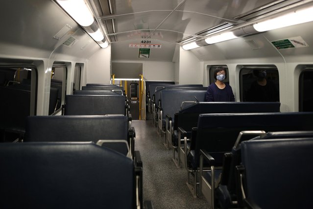 A lone commuter wearing a face mask sits in an empty train during morning rush hour after New South Wales began shutting down non-essential businesses and moving toward harsh penalties to enforce self-isolation in Sydney, Australia, March 24, 2020. (Photo by Loren Elliott/Reuters)
