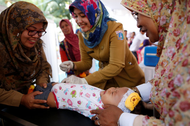 A child who received fake medication from a drug-making ring is revaccinated by government healthcare workers at a clinic in East Jakarta, Indonesia, July 18, 2016. (Photo by Darren Whiteside/Reuters)