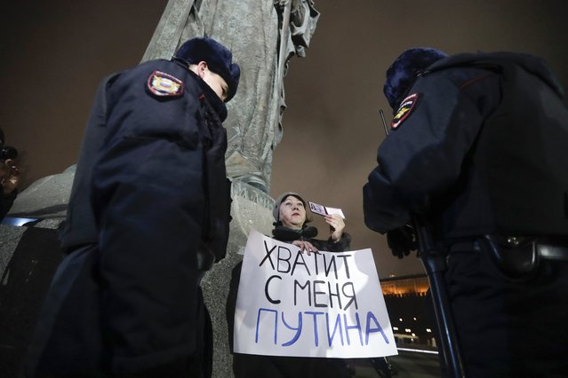 """Police officers check a protester's ID as she holds a poster that reads: """"Enough Putin for me"""" while taking part in a one-man protest in front of the monument of the Prince Vladimir next to the Kremlin in Moscow, Russia, Wednesday, March 11, 2020. The constitutional reform passed by the Duma on Wednesday would allow Putin to run for presidency two more times after 2024. Before the national vote, it will be reviewed by Russia's Constitutional Court. (Photo by Pavel Golovkin/AP Photo)"""
