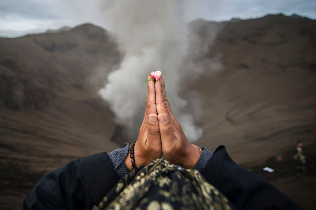 A Hindu devotee of the Tengger tribe prays during the Yadnya Kasada festival, on the crater of Mount Bromo in Probolinggo on July 21, 2016. (Photo by Juni Kriswanto/AFP Photo)