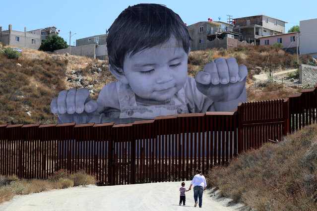 A small boy walks with his mother in front of French artist JR's image of an inquisitive baby looking into the United States over the U.S.- Mexico border wall towards Tecate, California, U.S., September 15,  2017. (Photo by Mike Blake/Reuters)