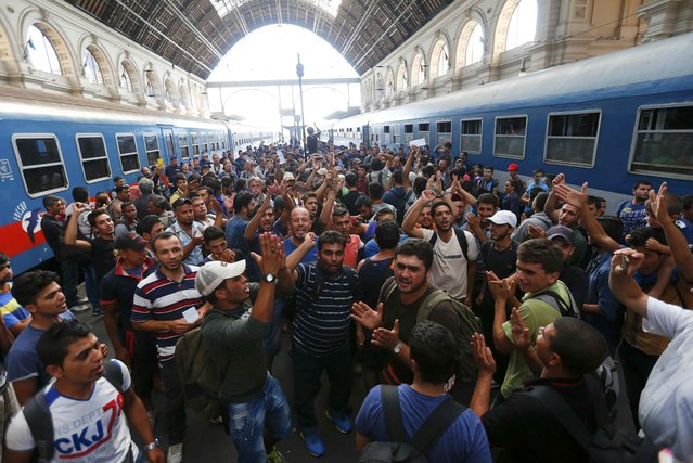 Migrants gesture as they stand in the main Eastern Railway station in Budapest, Hungary, September 1, 2015. Hungary closed Budapest's main Eastern Railway station on Tuesday morning with no trains departing or arriving until further notice, a spokesman for state railway company MAV said. There are hundreds of migrants waiting at the station. People have been told to leave the station and police have lined up at the main entrance, national news agency MTI reported. (Photo by Laszlo Balogh/Reuters)