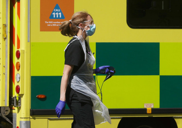 A medical worker wearing personal protective equipment (PPE) at the back of an ambulance outside Lewisham hospital as the spread of the coronavirus disease (COVID-19) continues, London, Britain, April 20, 2020. (Photo by Hannah McKay/Reuters)