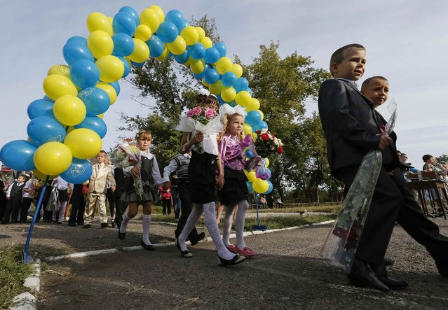 First graders take part in a festive ceremony to mark the start of another school year in Slaviansk, September 1, 2014. (Photo by Gleb Garanich/Reuters)