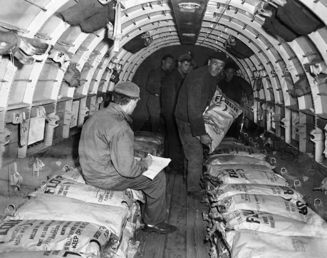 An American soldier of the air force checking loading list while a polish worker adds another sack of American flour to others already packed inside a C-47 transport plane at Frankfurt's Rhein-Main Airport, June 29, 1948, main base for the supply of Berlin by air. (Photo by Hanns J. Jaeger/AP Photo)