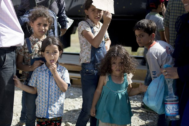 Migrant children look on as they wait to board a train after crossing the Macedonian-Greek border near Gevgelija, Macedonia, September 5, 2015. (Photo by Stoyan Nenov/Reuters)
