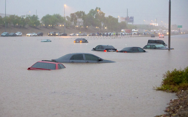 Cars are stuck in flood waters on I-10 east at 43rd Ave. in Phoenix after monsoon rains flooded the freeway Monday, September 8, 2014. Heavy storms pounded the Phoenix area early Monday, flooding major freeways, prompting several water rescues and setting an all-time single-day record for rainfall in the desert city. (Photo by Michael Chow/AP Photo/The Arizona Republic)
