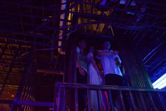 This picture taken on September 9, 2014 shows a waiter (R) and a group of people using an elevator at a prison themed restaurant in Tianjin. (Photo by Wang Zhao/AFP Photo)