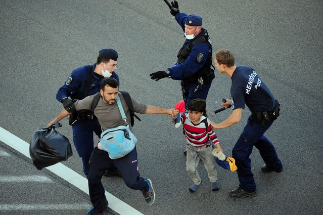 A migrant family is pushed down from the road by police on the M5 highway near Roszke village at the Hungarian-Serbian border on September 7, 2015. (Photo by Csaba Segesvari/AFP Photo)
