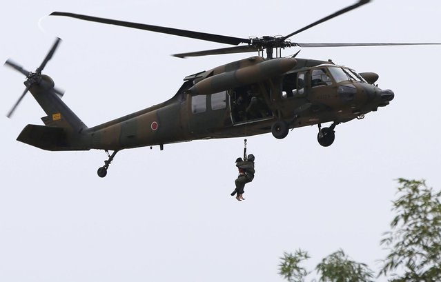 A resident (L) is rescued by a Japan Self-Defense Force (JSDF) helicopter at a residential area flooded by the Kinugawa river, caused by typhoon Etau, in Joso, Ibaraki prefecture, Japan, September 10, 2015. (Photo by Issei Kato/Reuters)