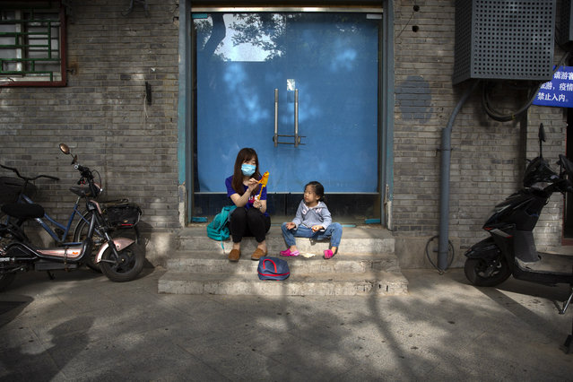 A woman wearing a face mask to protect against the spread of the new coronavirus shares a snack with a girl as they sit on a pedestrian shopping street in Beijing, Saturday, May 16, 2020. (Photo by Mark Schiefelbein/AP Photo)