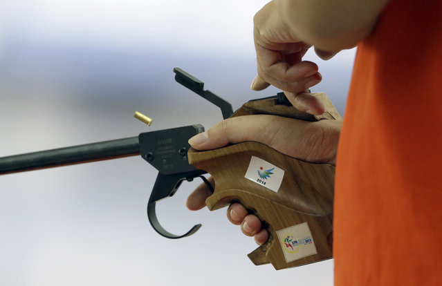 A bullet casing is expelled out of Vietnam's Nguyen Hoang Phuong in the final of the 50m Pistol Men at the Ongnyeon International Shooting Range for the 17th Asian Games in Incheon, South Korea, Saturday, September 20, 2014. (Photo by Lee Jin-man/AP Photo)