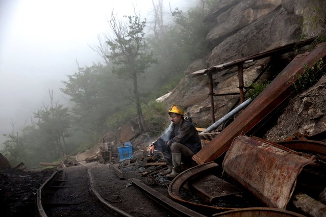 In this Thursday, May 8, 2014 photo, an Iranian coal miner takes a break at a mine near the city of Zirab 212 kilometers (132 miles) northeast of the capital Tehran, on a mountain in Mazandaran province, Iran. (Photo by Ebrahim Noroozi/AP Photo)