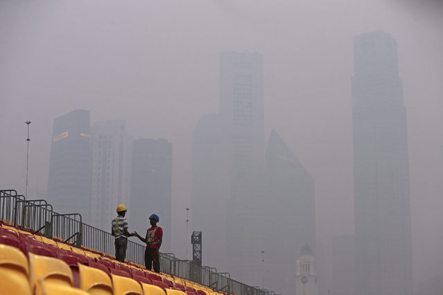 Construction workers on the spectator stands, pictured against the haze shrouded skyline of the financial district in Singapore, 14 September 2015. The National Environment Agency of Singapore today reported a 24-hour Pollutant Standards Index (PSI) reading of 152. Air quality with PSI reading between 101 and 200 is termed 'unhealthy' by the agency. The haze is caused by smoke from slash-and-burn farming practices in Indonesia and is blown across the Straits of Malacca by the seasonal monsoons. (Photo by Wallace Woon/EPA)