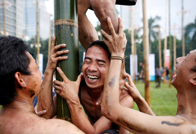 "Participants react as they climb a greased pole to collect vouchers for gifts during a ""Panjat Pinang"" event organised in celebration of Indonesia's 71st Independence day in Jakarta, Indonesia August 17, 2016. (Photo by Darren Whiteside/Reuters)"