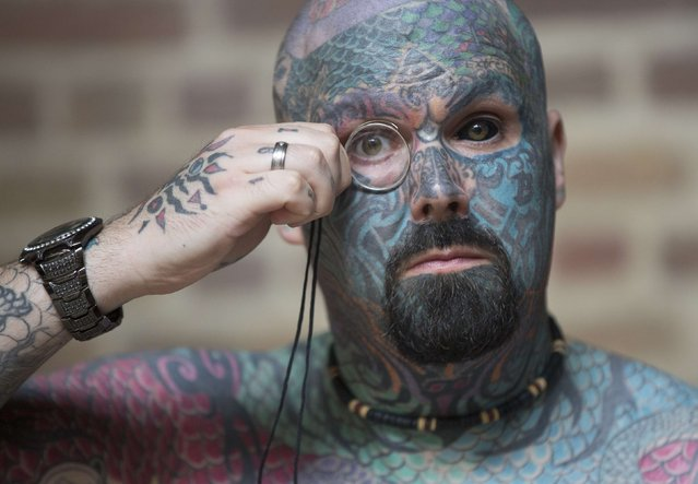 A man who has changed his name to King of Ink Land King Body Art The Extreme Ink-ite  adjusts his monocle as he poses during the 10th International Tattoo Convention in London September 27, 2014. (Photo by Neil Hall/Reuters)
