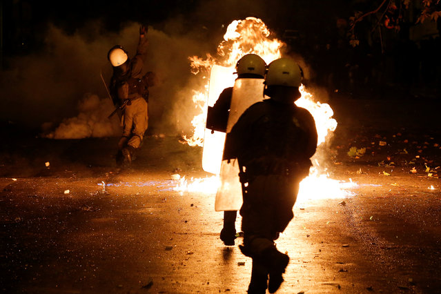 A petrol bomb explodes among riot policemen during clashes following a rally marking the 44th anniversary of a 1973 student uprising against the military dictatorship that was ruling Greece, in Athens, Greece, November 17, 2017. (Photo by Alkis Konstantinidis/Reuters)