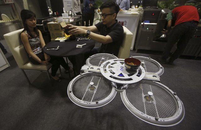 """Visitors are served by an Infinium-Serve Unmanned Aerial Vehicle (UAV) that is designed to serve food and wait tables, at the National Productivity Month exhibition in Singapore October 7, 2014. The UAV, a prototype designed by firm Infinium Robotics that specializes in UAV solutions, aims to free up restaurant staff to do """"higher value tasks"""" by accurately delivering food orders up to five kilograms to tables within a premise by means of anti-collision algorithms, according to Chief Executive Officer Woon Junyang. (Photo by Edgar Su/Reuters)"""
