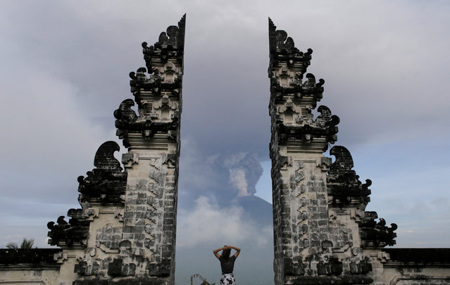 A tourist watches as Mount Agung volcano erupts at Lempuyang Temple in Karangasem, Bali, Indonesia on November 27, 2017. (Photo by Johannes P. Christo/Reuters)