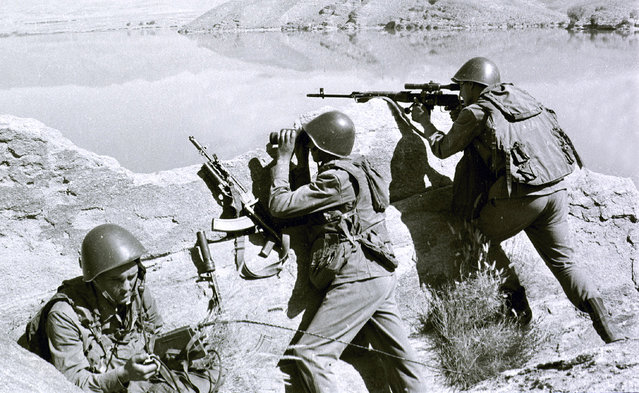 In this late April 1988, file photo, Soviet soldiers observe the highlands, while fighting Islamic guerrillas at an undisclosed location in Afghanistan. Moscow and Washington are intertwined in a complex and bloody history in Afghanistan, with both suffering thousands of dead and wounded in conflicts lasting for years. Now both superpowers are linked again over Afghanistan, with intelligence reports indicating Russia secretly offered bounties to the Taliban to kill American troops there. But analysts suggest that the two adversaries actually have more in common, especially when it comes to what they want to see in a postwar Afghanistan: a stable country that does not serve as a base for extremists to export terrorism. Both countries also are aligned in their opposition to militants from the Islamic State group. (Photo by Alexander Sekretarev/AP Photo/File)