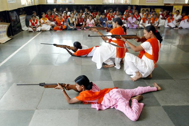 Women activists of the Vishwa Hindu Parishad or World Hindu Council, a hardline Hindu organisation, train in the art of shooting during a summer training camp, in Bombay May 17, 2003. (Photo by Sherwin Crasto/Reuters)