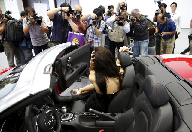 Visitors take pictures of a promotional woman posing in an Audi R8 Spyder during the Imported Auto Expo in Beijing, China, September 24, 2015. The auto show goes on till September 28th. (Photo by Kim Kyung-Hoon/Reuters)
