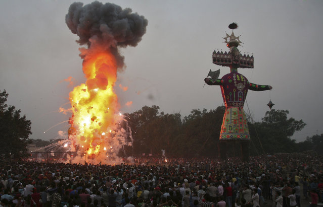 People watch as an effigy of 10-headed demon King Ravana is burnt during the Hindu festival of Dussehra in Amritsar October 3, 2014. (Photo by Munish Sharma/Reuters)