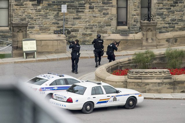 Police teams enter Centre Block at Parliament Hill in Ottawa on  Wednesday October 22, 2014. (Photo by Justin Tang/AP Photo/The Canadian Press)