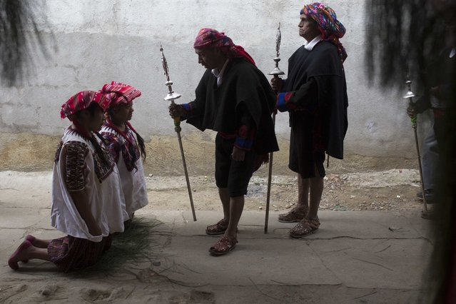 Women kneel to welcome the guardians of St. Thomas' to the home where the statue of the Catholic icon has been under the care of a family, during festivities in honor of the patron Saint of Chichicastenango, Guatemala, Monday, December 18, 2017. The ongoing celebration honors the Mayan town's patron saint until Dec. 23. (Photo by Luis Soto/AP Photo)