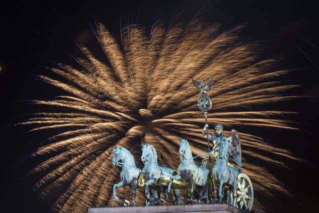 Fireworks explode in the sky above the  Quadriga on the Brandenburg Gate during the New Year's celebrations in Berlin, Tuesday, Jan. 1, 2013. (Photo by Markus Schreiber/AP Photo)
