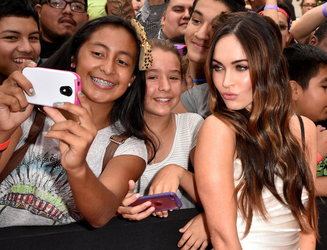 "Actress Megan Fox (R) takes a selfie with fans at the premiere of Paramount Pictures' ""Teenage Mutant Ninja Turtles"" at Regency Village Theater on August 3, 2014 in Westwood, California. (Photo by Kevin Winter/Getty Images for Paramount Pictures)"
