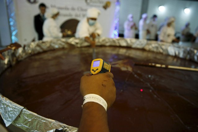 A worker measures chocolate temperature during the cooking process of a chocolate coin in an attempt to break the Guinness World Record for the biggest chocolate coin in Caracas, Venezuela, October 1, 2015. (Photo by Carlos Garcia Rawlins/Reuters)