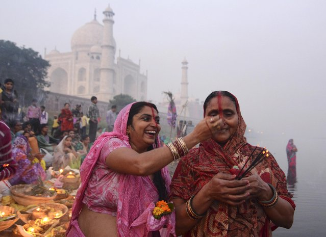 A woman laughs as she smears vermilion on the forehead of another woman while worshipping the Sun god Surya against the backdrop of the historic Taj Mahal during the Hindu religious festival of Chatt Puja in the northern Indian city Agra October 30, 2014. (Photo by Brijesh Singh/Reuters)