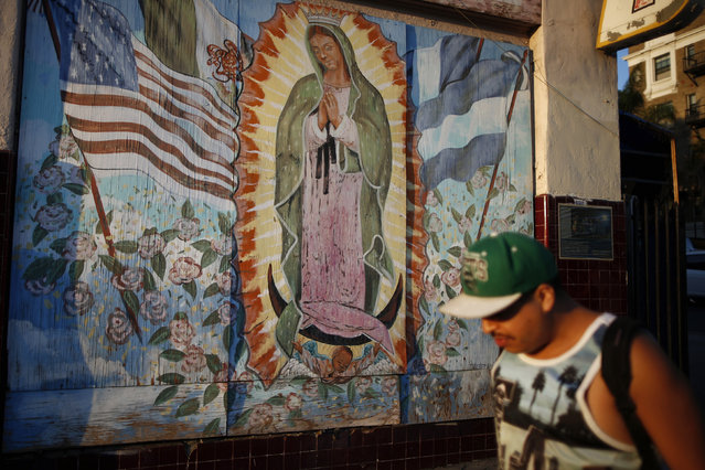 A man walks past a mural showing the Mexican, Salvadoran, Guatemalan and United States flags surrounding the Virgin of Guadalupe, patroness of the Americas, in the Westlake area of Los Angeles, home to many Mexican and Central American migrants, in California August 6, 2014. (Photo by Lucy Nicholson/Reuters)