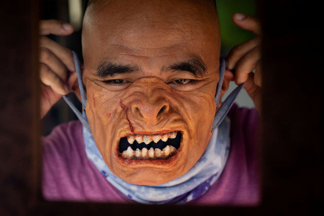 TV prosthetics artist Rene Abelardo tries on a sample of his prosthetic face mask, his latest creation as TV projects took a halt amid the coronavirus disease (COVID-19) outbreak, in San Pedro, Laguna, Philippines, June 17, 2020. (Photo by Eloisa Lopez/Reuters)