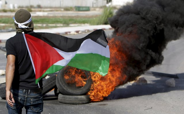 A Palestinian protester holds a Palestinian flag as he takes cover behind a burning tyre during clashes with Israeli troops in the West Bank city of Jenin October 9, 2015. (Photo by Mohammed Ballas/Reuters)