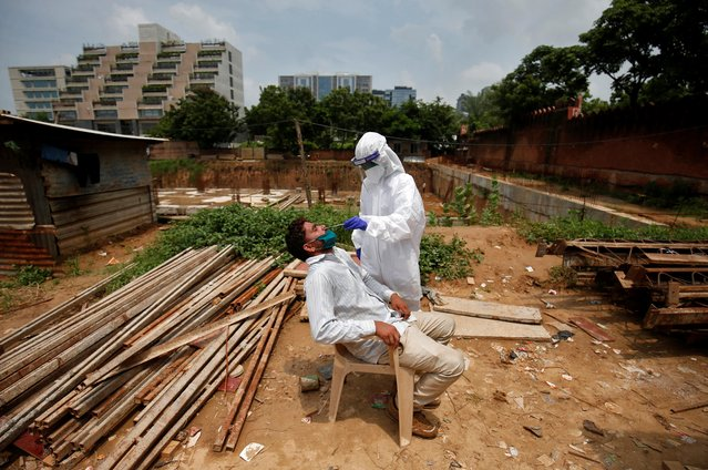 A healthcare worker wearing personal protective equipment (PPE) takes a swab from a labourer for a rapid antigen test at a construction site, amidst the coronavirus disease (COVID-19) outbreak, in Ahmedabad, India, September 3, 2020. (Photo by Amit Dave/Reuters)
