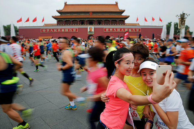 Participants take pictures of themselves as others run past the Tiananmen gate during the Beijing Marathon in Beijing, China, September 17, 2016. (Photo by Damir Sagolj/Reuters)