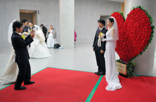 """A couple has their photograph taken during a mass wedding organised by the Unification Church in Gapyeong on February 17, 2013. Some 3,500 couples married in a mass wedding organised by the Unification Church on February 17 – the first such event since the death of their """"messiah"""" and controversial church founder Sun Myung Moon. (Photo by Kim Jae-Hwan/AFP Photo)"""