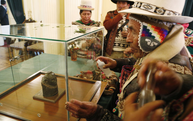 Indigenous Andean spiritual counselors known as Amautas spray alcohol on the case protecting a pre-Columbian relic made of carved stone during its presentation at the presidential palace after it was returned from Switzerland, in La Paz, Bolivia, Monday, November 17, 2014. Bolivia recovered the 2000 year old relic after it had been in Switzerland for 156 years. According to experts, it's a woman representing an Ekeko Andean deity, god of fertility and abundance, from the Pucara culture that inhabited the Lake Titicaca region. (Photo by Juan Karita/AP Photo)